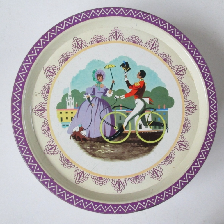 The Qualioty Street Soldier, ridimng a boneshaker bicycle, greets the Lady